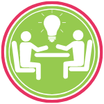 GoFish! Branded Services Icon - PR Counsel & Expertise - White background, circle in shape. A pink ring frames the logo, encompassing a smaller green ring, and within the green ring there is a green circle. In the centre circle two generic person figures are sitting on chairs facing each other over a line meant to signify a tabletop. Their arms are akimbo over the table top, as though in animated conversation. Between them, floating above the table, is a large white lightbulb with lines coming out from the bulb, indicating light beams.
